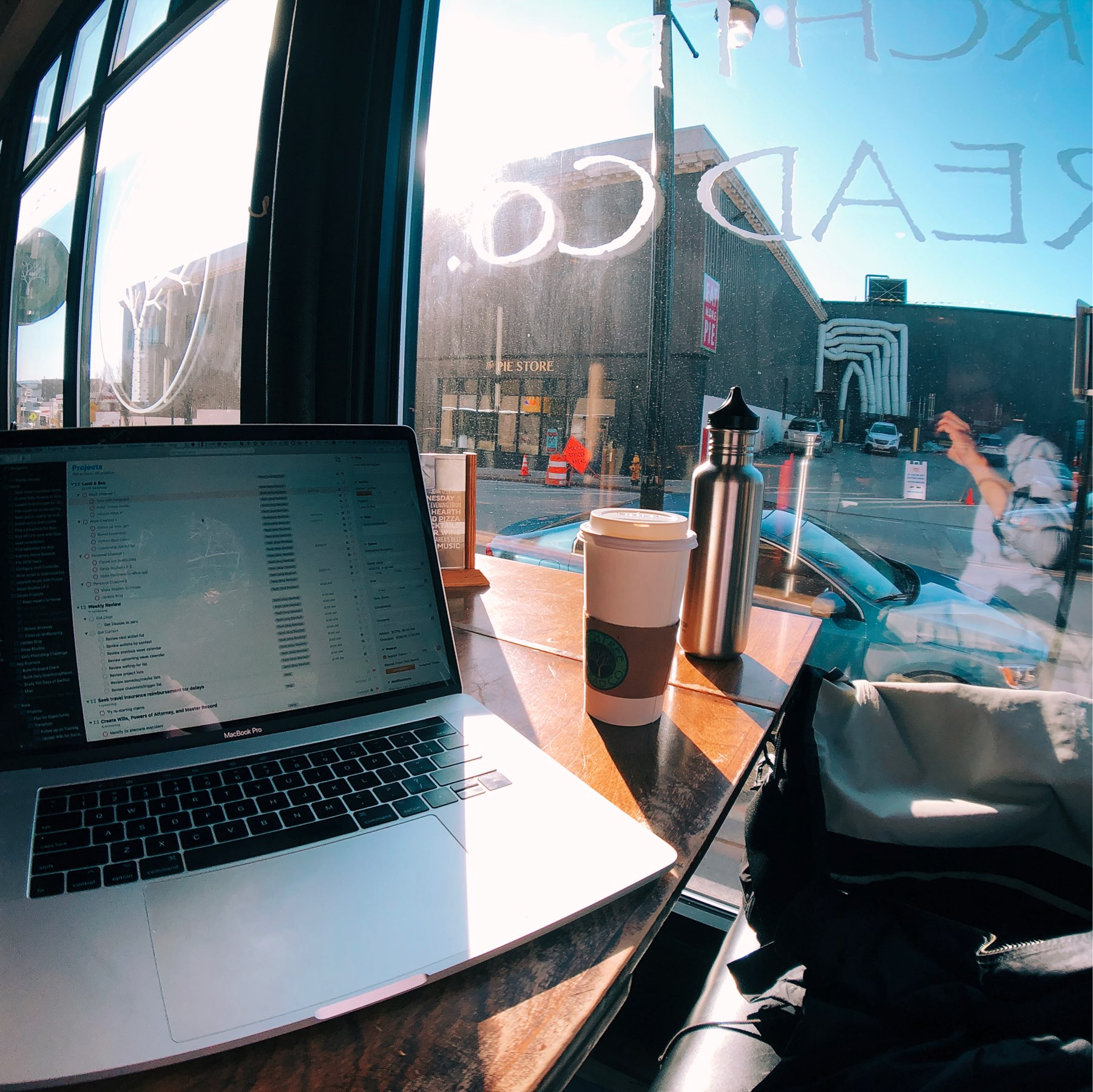 Laptop in sun at coffee shop.