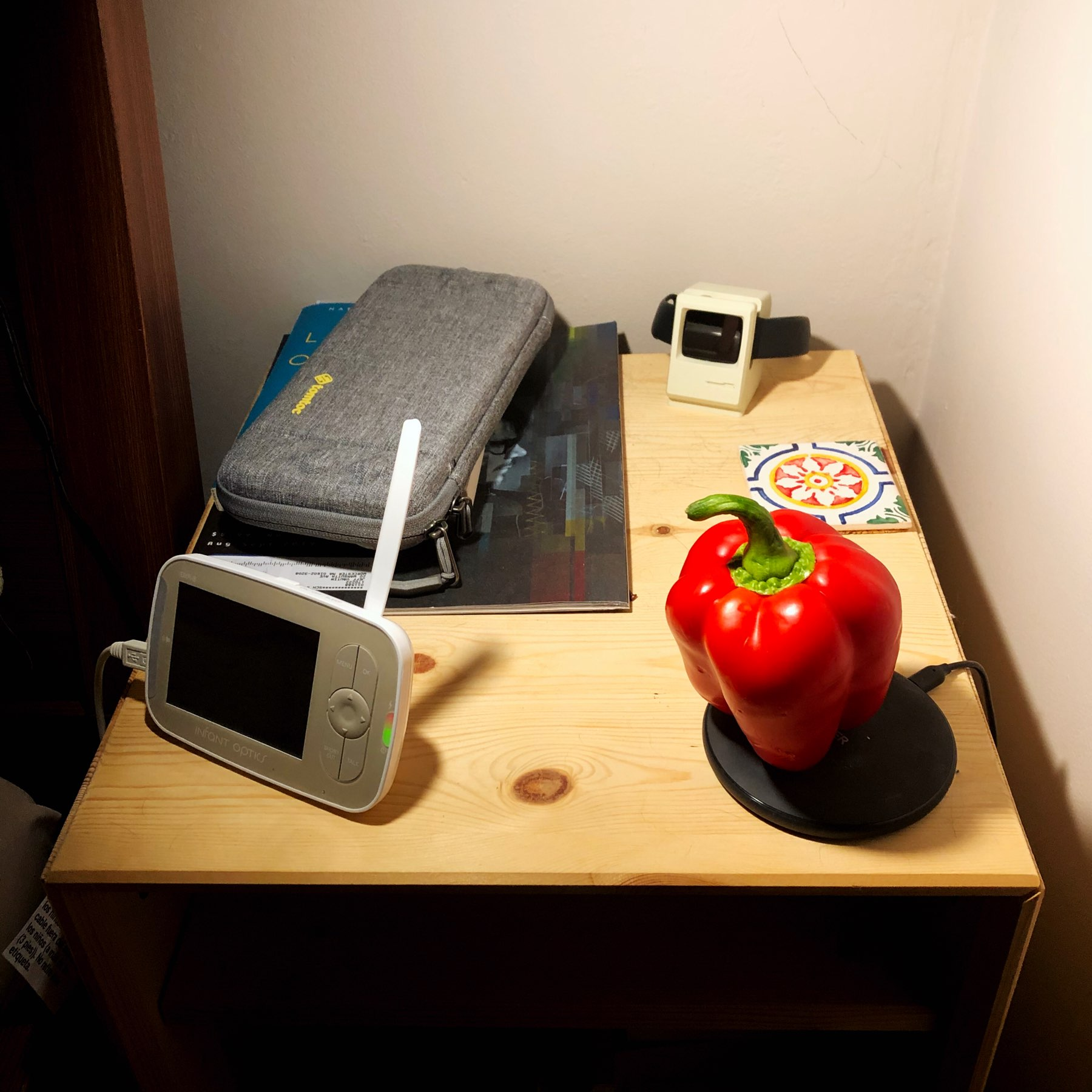 Nightstand with red pepper balanced on a phone charger.