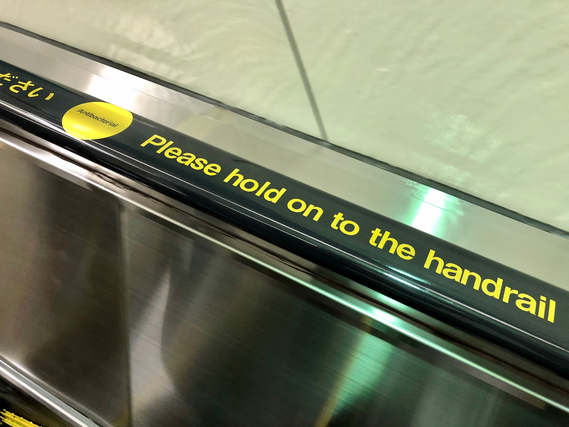 "Escalator handrail with inscription, ""Antibacterial - Please hold handrail"""