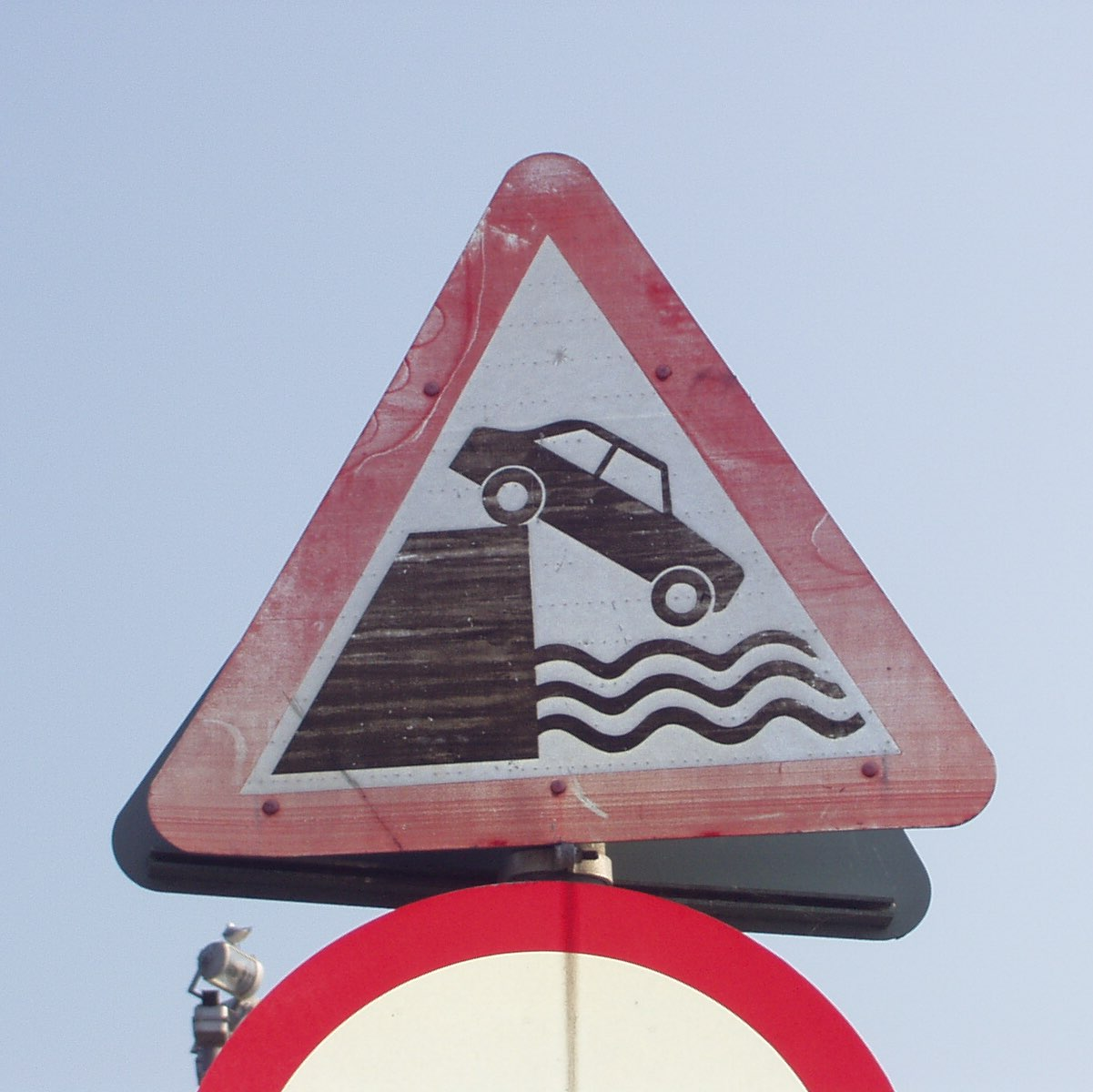 Sign depicting car driving into water.